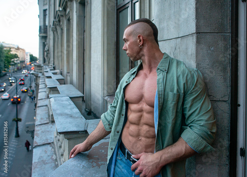 Obraz Handsome shirtless muscular young man outdoor on a balcony - fototapety do salonu