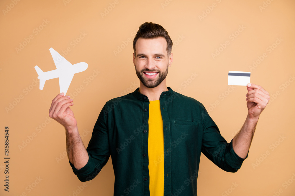 Fototapeta Honey, it's vacation time. Photo of nice hipster guy holding credit card paper air plane demonstrating girlfriend good news wear casual outfit isolated beige color background