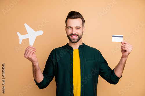 Fototapeta Honey, it's vacation time. Photo of nice hipster guy holding credit card paper air plane demonstrating girlfriend good news wear casual outfit isolated beige color background obraz