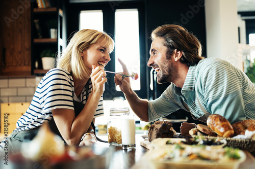 Obraz Beautiful young couple is smiling while cooking together in kitchen at home - fototapety do salonu