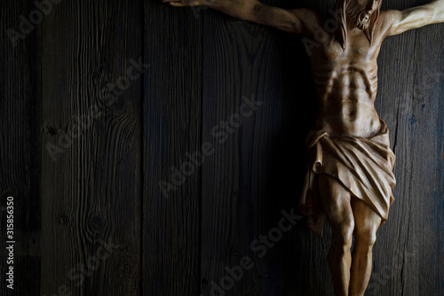 Cruciefied Jesus figure isolated on rustic dark brown table. Canvas Print