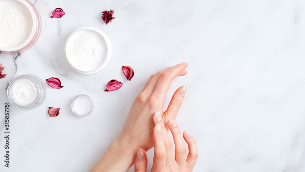 Fototapeta Hand skin care concept. Top view female hands applying organic moisturizing hand cream, jars with cosmetic cream and pink petal on marble table. Natural organic beauty products