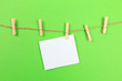 Leinwandbild Motiv a piece of white paper attached to a rope clothespin on green background  - Image