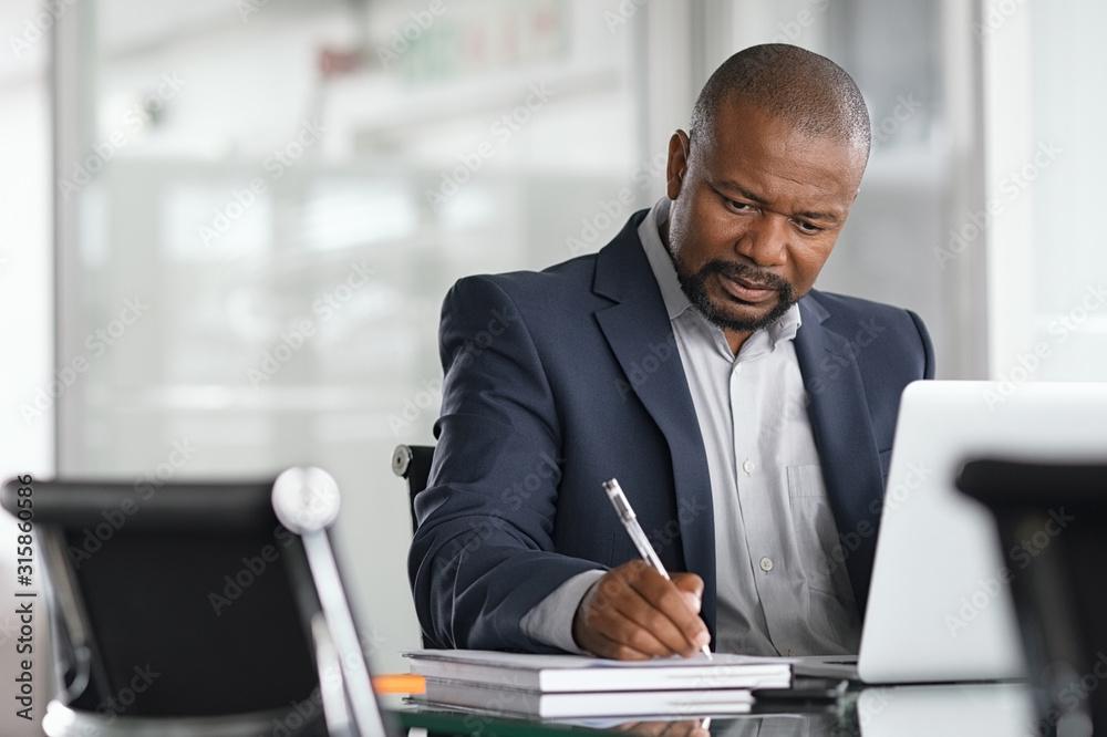 Fototapeta Mature businessman writing on documents
