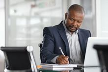 Mature Businessman Writing On ...