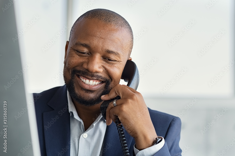 Fototapeta Mature black business man talking on phone