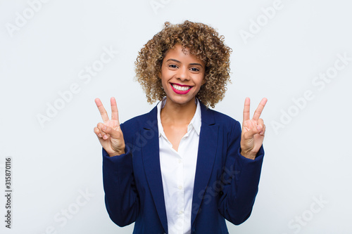 young woman african american smiling and looking happy, friendly and satisfied, gesturing victory or peace with both hands against flat wall
