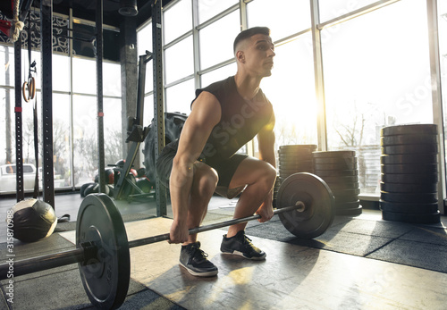Professional. Young muscular caucasian athlete training in gym, doing strength exercises, practicing, work on his upper body with weights and barbell. Fitness, wellness, healthy lifestyle concept. - 315870988