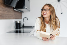 Photo Of Young Happy Woman Reading Book And Smiling