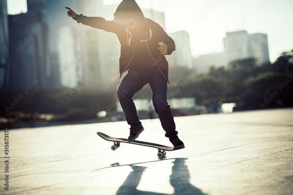 Fototapeta Skateboarder skateboarding at sunset city