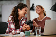 canvas print picture - Young woman showing colleague pictures in camera. Two beautiful businesswomen having fun in office.