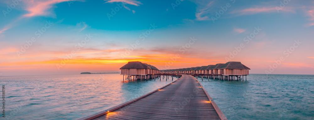 Fototapeta Maldives island sunset. Water bungalows resort at islands beach. Indian Ocean, Maldives. Beautiful sunset landscape, luxury resort and colorful sky. Artistic beach sunset under wonderful sky