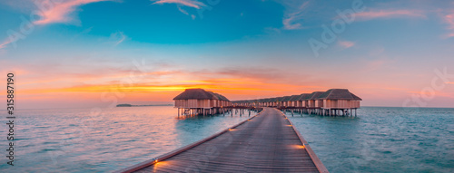 Obraz Maldives island sunset. Water bungalows resort at islands beach. Indian Ocean, Maldives. Beautiful sunset landscape, luxury resort and colorful sky. Artistic beach sunset under wonderful sky - fototapety do salonu