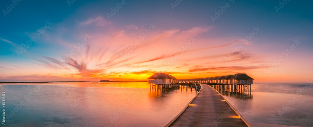 Fototapeta Sunset on Maldives island, luxury water villas resort and wooden pier. Beautiful sky and clouds and beach background for summer vacation holiday and travel concept