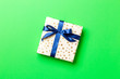 canvas print picture - wrapped Christmas or other holiday handmade present in paper with blue ribbon on green background. Present box, decoration of gift on colored table, top view with copy space