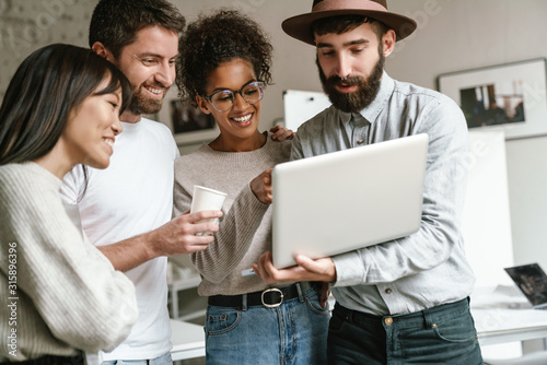 Image of multiethnic young business workers standing together at office Canvas Print