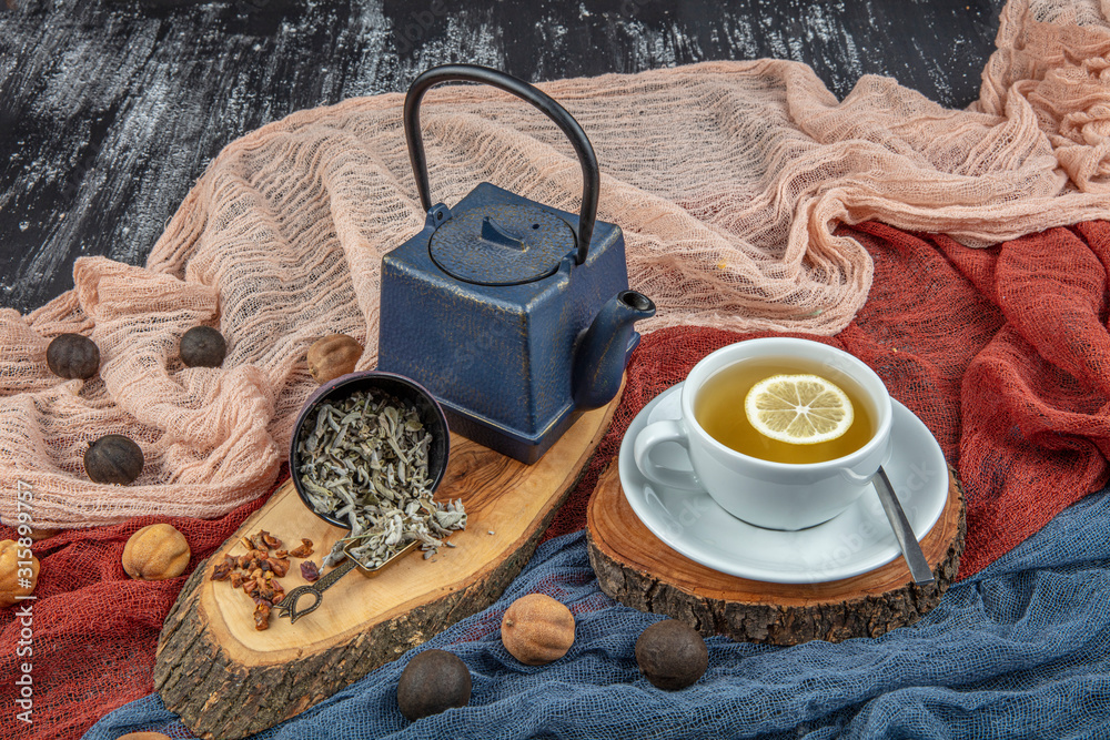 Fototapeta Still life with traditional sage tea prepared in vintage cast iron teapot on rustic wooden table. Retro filter.