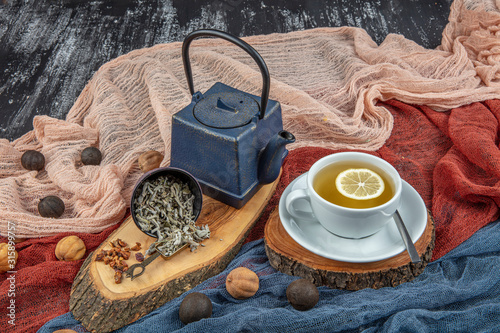 Fototapeta Still life with traditional sage tea prepared in vintage cast iron teapot on rustic wooden table. Retro filter. obraz