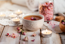 Concept Of Spa Treatment With Roses. Herbal Tea, Crystals Of Sea Pink Salt In Bottle, Candles As Decor. Atmosphere Of Relax, Anti-stress And Detox Procedure. Luxury Lifestyle. Wooden Background