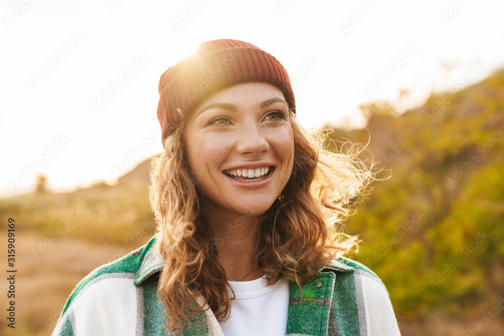 Fototapeta Image of young woman wearing hat and plaid shirt walking outdoors