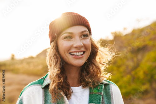 Fotografia Image of young woman wearing hat and plaid shirt walking outdoors