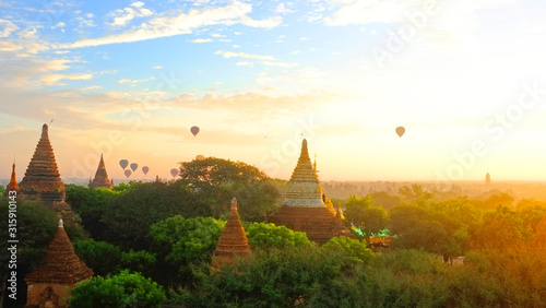 Photo Sunrise in Bagan Archeologial Zone, Myanmar top view with hot air ballooons flying on a horizont