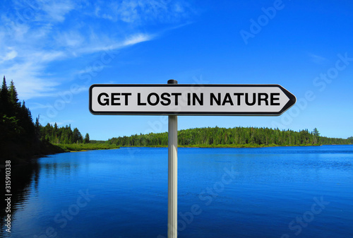 Fotomural  Road sign with GET LOST IN NATURE text under lake background
