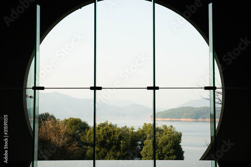 Beautiful lake view through the chinese arch wall and glass window
