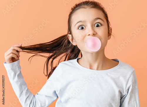 Valokuva Cute little girl with chewing gum on color background