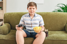 Overweight Boy With Chips Playing Video Game At Home