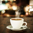 canvas print picture - Fresh hot coffee on wooden table in cafe interior and free space for your decoration.