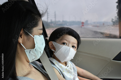 Fototapeta mother and kid wearing face mask protect air dust pollution with pm 2.5 obraz