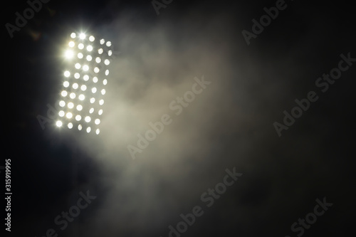 Fototapeta stadium lights and smoke against dark night sky background obraz