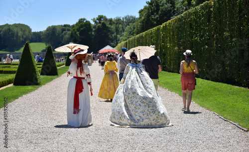 Unidentified people costumed in the fashions of the 17th french aristocracy, walking in French formal gardens Wallpaper Mural