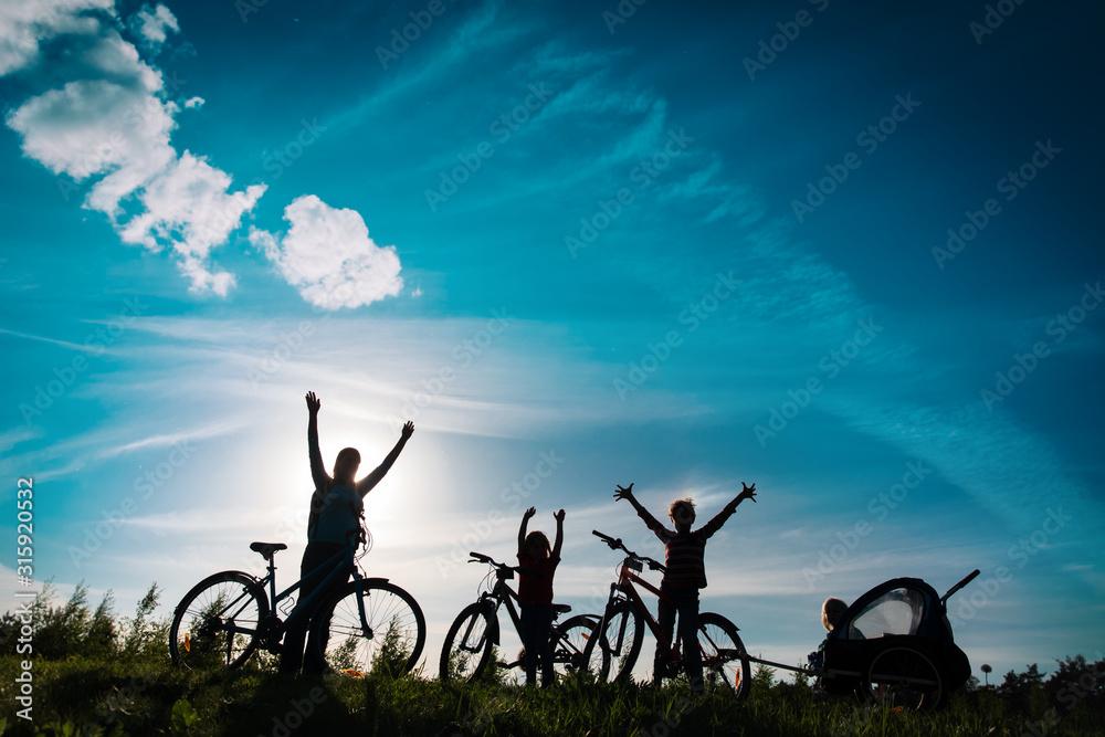 Fototapeta Happy mother with kids biking at sunset, family enjoy bike ride