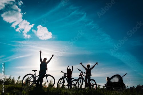 Happy mother with kids biking at sunset, family enjoy bike ride Canvas