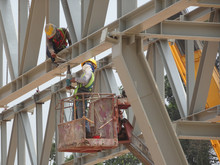Construction Workers Working At Height Installing The Steel Structure. Steel Structure Able To Provide Huge And Long Span For The Building.