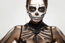 Brunette Girl With Skull Makeup For Halloween On A Black Background