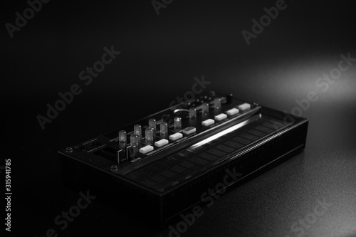 Photo small analog fm modulation synthesizer, with knobs and faders, with effects, arp
