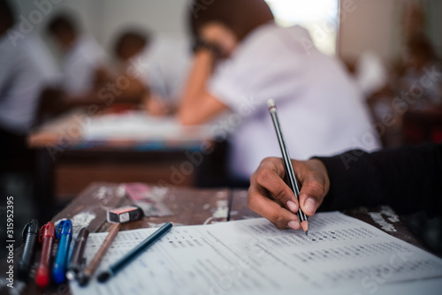 Fotomural  Students taking exam with stress in school classroom.