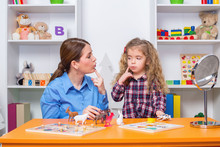 Young Girl  In Speech Therapy Office. Preschooler Exercising Correct Pronunciation With Speech Therapist.