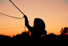 Silhouette Of Young Cowboy Roping Against Sunset Sky Background, Ranch Rodeo Lifestyle Kid Concept.