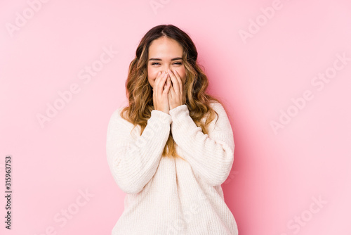 Fototapeta Young curvy woman posing in a pink background isolated laughing about something, covering mouth with hands. obraz