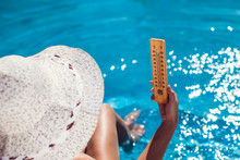 Woman Holding Thermometer On The Pool Background. Hot Weather And Summer Concept