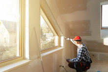 Home Improvement Handyman Filling Drywall With Filler In New Build Attic