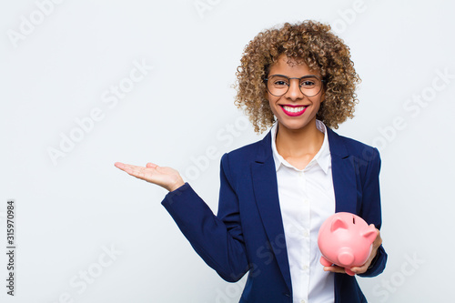 Obraz young african american woman smiling cheerfully, feeling happy and showing a concept in copy space with palm of hand with a piggy bank - fototapety do salonu