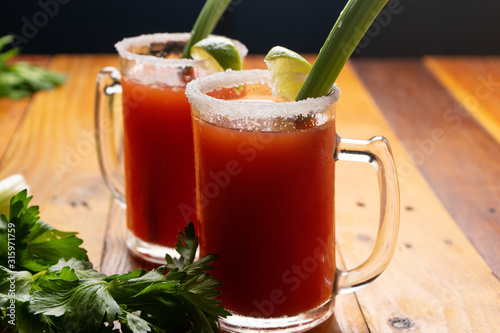 Mexican beer cocktail called michelada with celery on wooden background