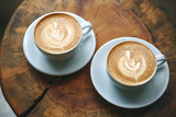 Two cups of aromatic coffee cappuccino or latte on a wooden table. Tasty morning drinks.