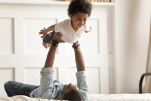 Cute Funny Black Boy Flying In Strong Fathers Hands.