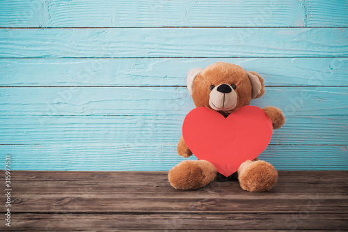 Tela Teddy bear with red heart on old wooden background. Valentine's